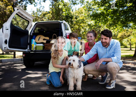 Portrait of happy family sitting in the park with their dog - Stock Photo