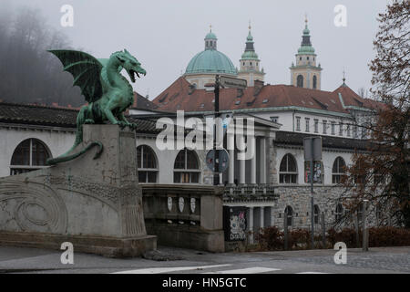 One of the dragon sculptures of the Dragon Bridge in front of the Central Market and the Cathedral of St. Nicholas. - Stock Photo