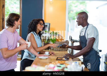 Woman entering pin code on credit card reader at counter in café - Stock Photo