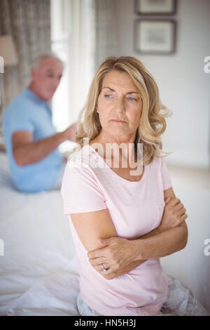 Upset senior couple arguing in bedroom at home - Stock Photo