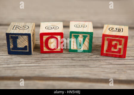 Blocks displaying love message on wooden surface - Stock Photo