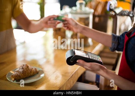 Mid-section of customer making payment through credit card at counter in café - Stock Photo