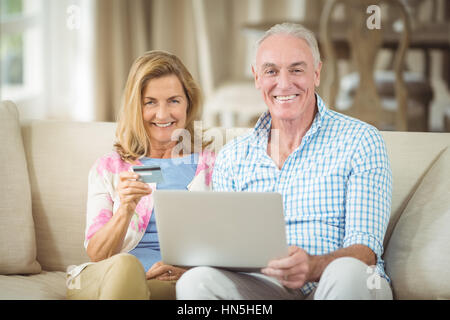 Portrait of smiling senior couple doing online shopping on laptop in living room at home - Stock Photo