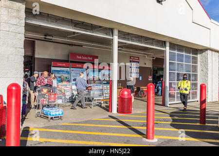 Fairfax, USA - December 3, 2016: People with shopping carts filled with groceries walking out of Costco store in - Stock Photo