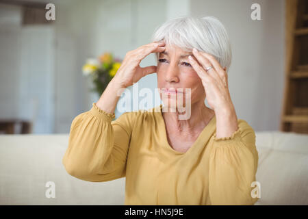Senior woman suffering from head ache in living room at home - Stock Photo