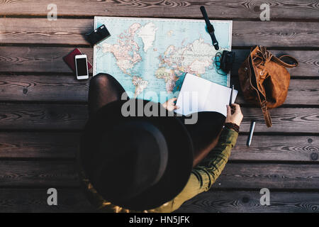 Top view of woman wearing hat making tour plan using a world map. Tourist exploring the world map with travel accessories - Stock Photo