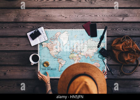 Young woman planning vacation using world map and compass along with other travel accessories. Tourist wearing brown - Stock Photo