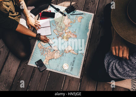 Man and woman discussing tour plans using the world map. Woman making notes and pointing on the map while the man - Stock Photo