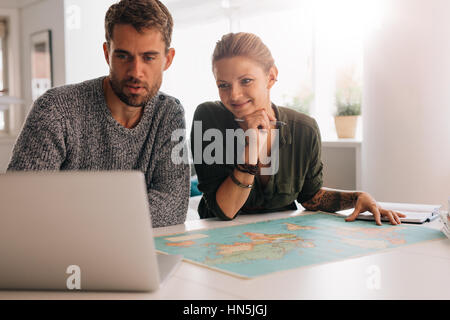 Young man and woman looking at laptop computer with world map in front. Couple using technology to explore the world. - Stock Photo