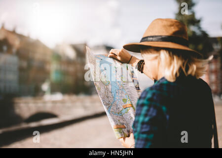Side view of young woman wearing hat looking at a city map. Tourist looking for navigation route on map.