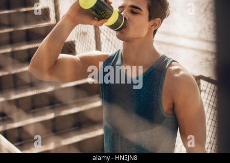 Shot of muscular young man drinking water by the beach after workout. Runner drinking water after exercising and - Stock Photo