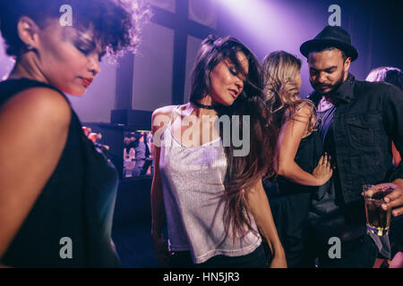 Young woman dancing at party with friends near by. Group of young people having fun at nightclub. - Stock Photo