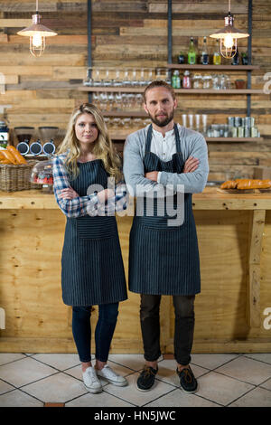 Portrait of waiter and waitress standing with arms crossed at counter in café - Stock Photo