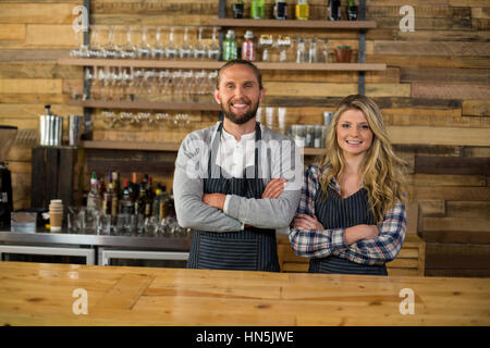 Portrait of smiling waiter and waitress standing with arms crossed at counter in café - Stock Photo