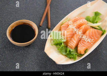 Sushi on boat shaped plate with chopsticks and sauce - Stock Photo