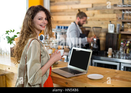 Portrait of woman standing at counter and using laptop while having coffee in café - Stock Photo