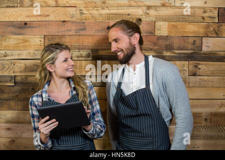 Smiling waiter and waitress using digital tablet against wooden wall in cafe - Stock Photo