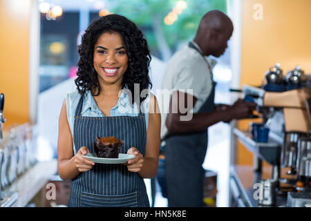 Portrait of smiling waitress holding a plate of cupcake in café - Stock Photo