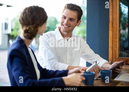 Businessman and woman interacting while having coffee at counter in café - Stock Photo
