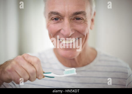 Portrait of senior man brushing his teeth in bathroom at home - Stock Photo