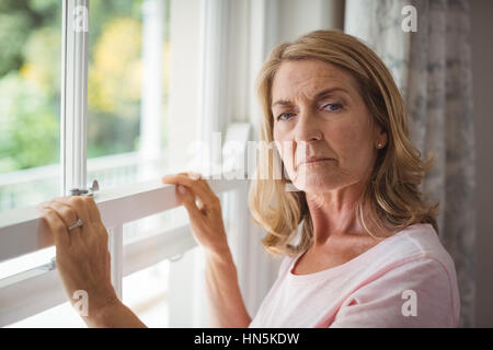 Portrait of senior woman standing next to window at home - Stock Photo