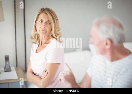 Worried senior woman sitting on bed in bedroom - Stock Photo