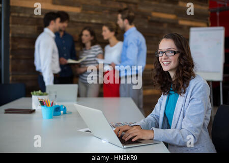 Female graphic designer using laptop in office - Stock Photo