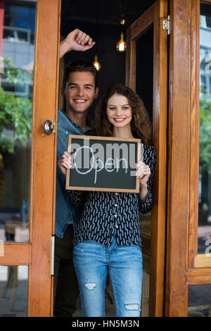 Portrait of man and woman showing chalkboard with open sign at café - Stock Photo