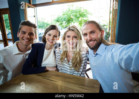Portrait of young friends having fun in café - Stock Photo