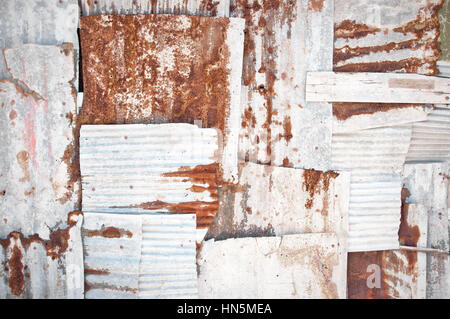 An abstract background image of rusting white corrugated iron sheets overlapping to form a wall or fence. - Stock Photo