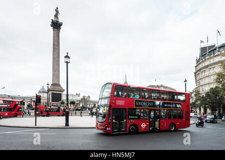 London, United Kingdom - October 20, 2016: Buses are passing by Trafalgar Square in London, UK - Stock Photo