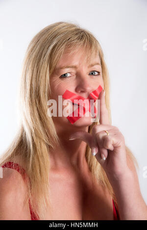 Woman with red tape strtched across her mouth - Stock Photo
