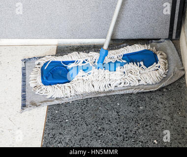Dirty old mop with the dust on the office floor. - Stock Photo