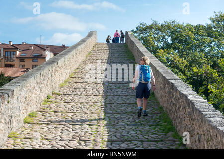 A woman tourist walks over the Roman Bridge of Cangas de Onis an ancient stone bridge over the river Sella in the - Stock Photo
