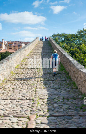 A woman tourist walks over the Roman Bridge of Cangas de Onis an ancient stone bridge over the river Sella in the - Stock Photo