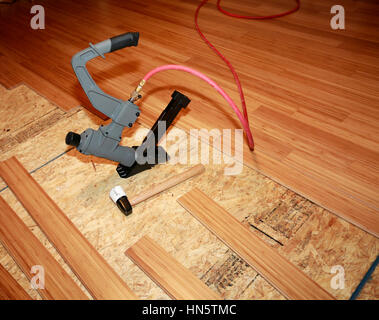 Installing of beautiful bamboo hardwood floor with pneumatic tool - Stock Photo