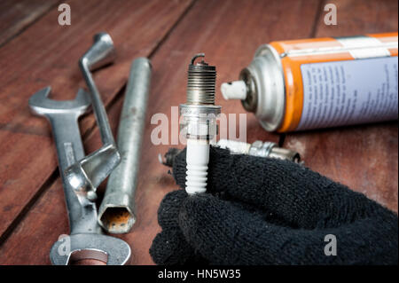 used spark plug with soot in technician hand - Stock Photo