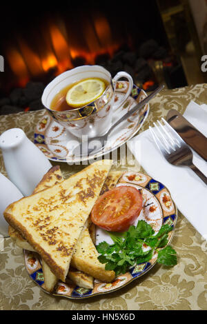 An English breakfast dish of Gypsy Toast served with grilled Tomato, garnished with fresh Parsley. - Stock Photo