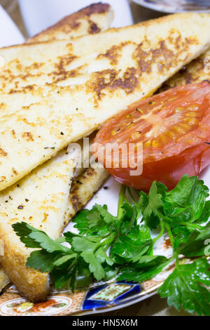 Close up of a portion of Gypsy Toast served with grilled Tomato and Parley garnish. - Stock Photo