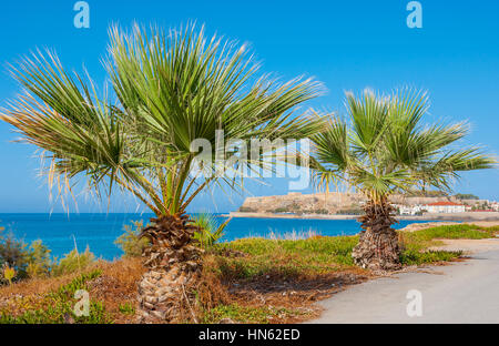 The view on medieval Venetian fortress through palms in Rethymno, Greece - Stock Photo