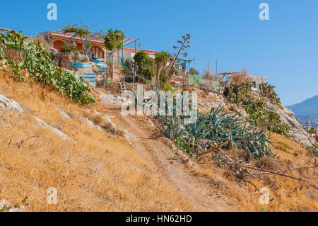 The small residential house with garden located on the fortress hill slopes in Rethymno, Greece - Stock Photo