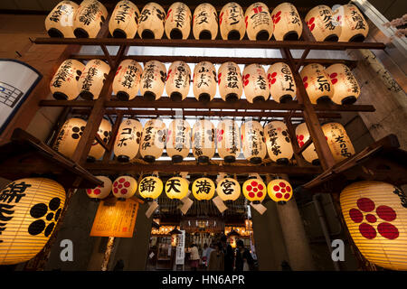 Kyoto, Japan - March 20, 2012: Illuminated paper lanterns hanging above the entrance of Nishiki Tenmangu Shrine - Stock Photo