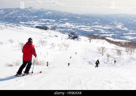 Niseko, Japan - March 4, 2012: Wide view showing skiers, slopes and lifts on Mount Annupuri in the ski resort of - Stock Photo