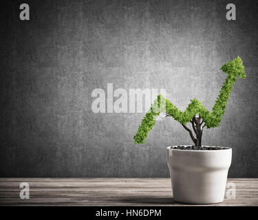 Small plant in pot shaped like growing graph - Stock Photo