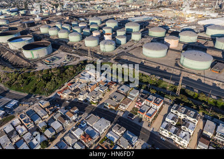 Los Angeles County, California, USA - December 17, 2016:  Middle class homes below large oil refinery tanks in Southern - Stock Photo