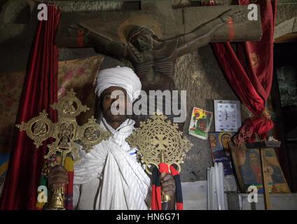 Portrait of an ethiopian orthodox priest holding crosses inside Asheten mariam rock hewn church, Amhara region, - Stock Photo