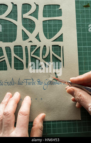 Calligraphy studio, hand holding scalpel with paper cutting, sheet with text from paper cutting, Seebruck, Upper - Stock Photo