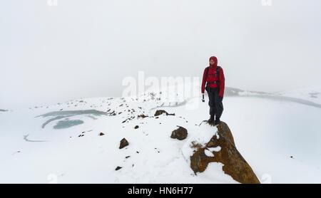 Hiker standing on rock, Frozen Emerald Lakes, Tongariro Alpine Crossing with snow, Tongariro National Park, Southland - Stock Photo