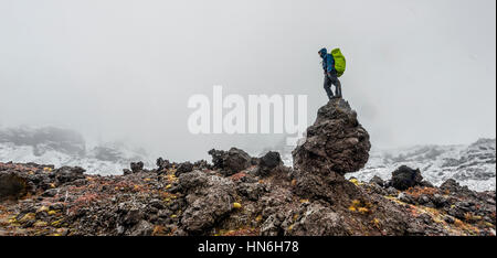 Hiker standing on rock, Tongariro Alpine Crossing with snow, Tongariro National Park, Southland, New Zealand - Stock Photo