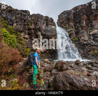 Hiker the Taranaki Falls, waterfall, Tongariro National Park, North Island, New Zealand - Stock Photo